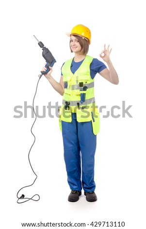 smiling construction female worker in yellow hardhat and reflective vest holding a drill and showing okay sign isolated on white background. proposing service. advertisement gesture