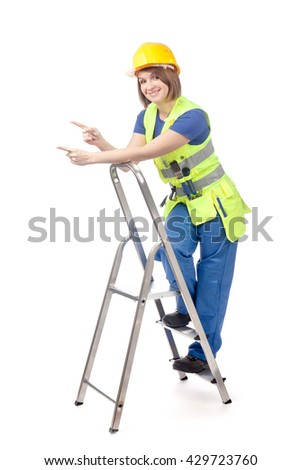smiling construction female worker in yellow helmet and reflective vest with ladder  pointing on empty copy space for text isolated on white background. proposing service. advertisement gesture - stock photo