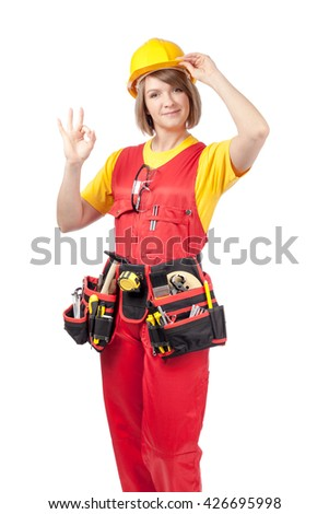 smiling construction female worker in yellow helmet, toolbelt and red workwear showing okay sign isolated on white background. proposing service. advertisement gesture - stock photo
