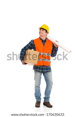 Smiling construction worker holds paper roll on his shoulder and carton box under his arm. Full length studio shot isolated on white.