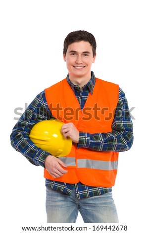 Smiling construction worker in orange reflective waistcoat with yellow helmet under the arm. Three quarter length studio shot isolated on white. - stock photo