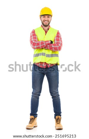 Smiling construction worker in yellow helmet and lime waistcoat posing with arms crossed. Full length studio shot isolated on white.