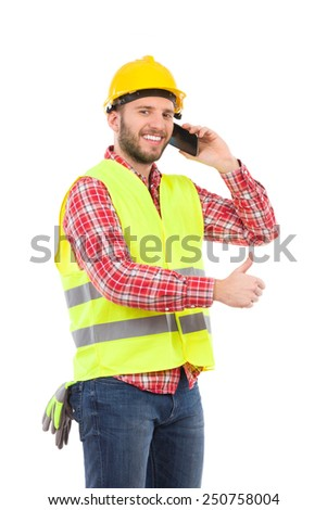 Smiling construction worker in yellow helmet and lime waistcoat posing with cell phone and showing thumb up. Three quarter length studio shot isolated on white. - stock photo