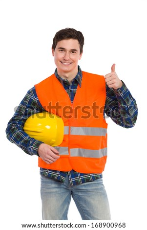 Smiling construction worker in yellow helmet and orange reflective waistcoat showing thumb up. Three quarter length studio shot isolated on white. - stock photo
