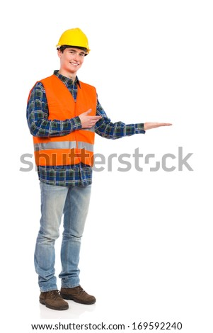 Smiling construction worker in yellow helmet and orange waistcoat standing and presenting product.  Full length studio shot isolated on white.