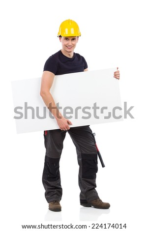 Smiling construction worker standing and holding banner under his arm. Full length studio shot isolated on white. - stock photo