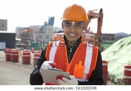 Smiling construction worker standing on construction   site - stock photo