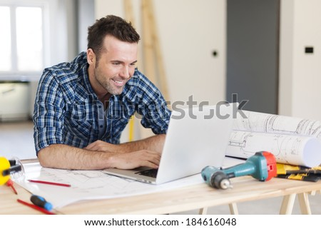 Smiling construction worker working with laptop  - stock photo