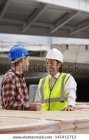 Smiling construction workers talking at the building site