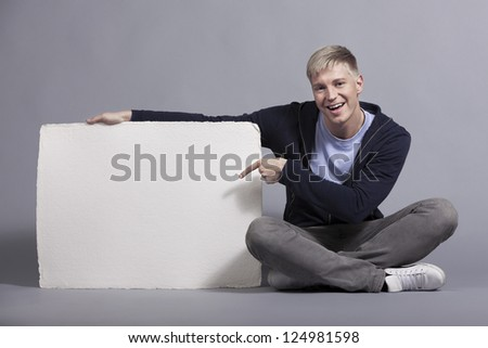 Smiling content man pointing finger at white empty signboard with space for text while holding it isolated on grey background. - stock photo