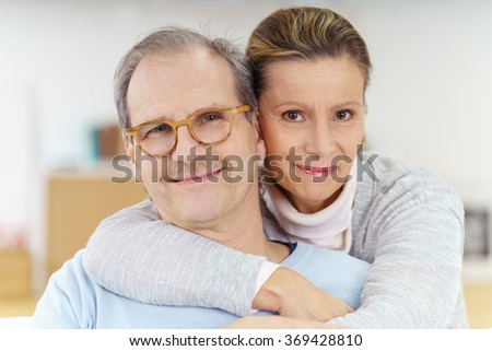 Smiling contented middle-aged man wearing glasses being hugged from behind by his wife as they relax together on the sofa at home