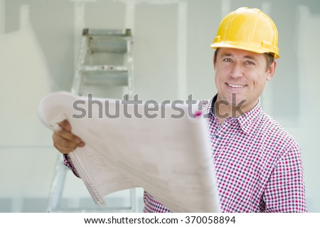 Smiling Contractor Holding Blueprints Inside Home Construction Site. - stock photo