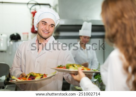 Smiling cook gives to waitress dishes with meal at kitchen - stock photo