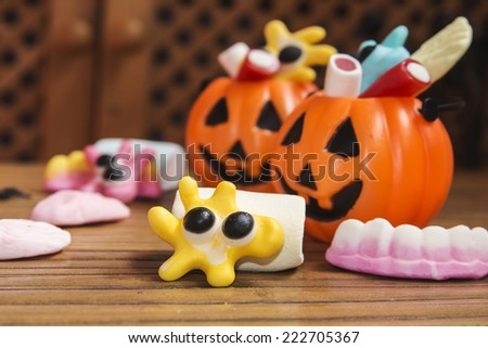 Smiling cookies with candies and pumpkins in Halloween festivities