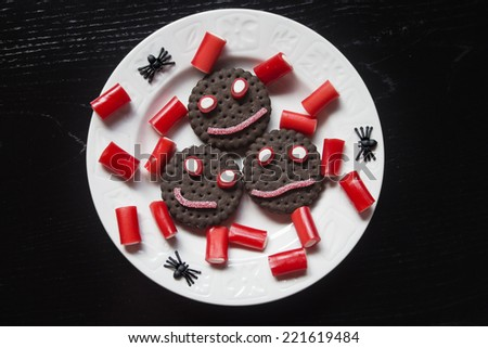 Smiling cookies with candies and spiders in Halloween festivities - stock photo