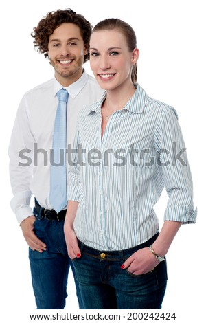 Smiling corporate executives posing with hands in pockets