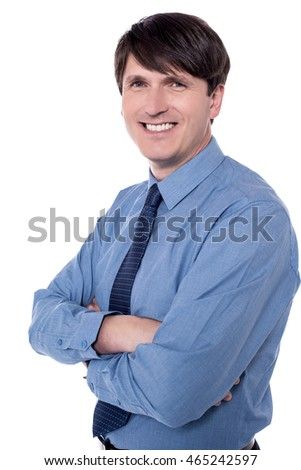 Smiling corporate guy posing with arms crossed.
