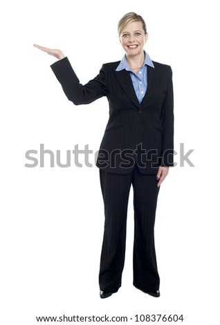 Smiling corporate lady presenting copy space, full length portrait
