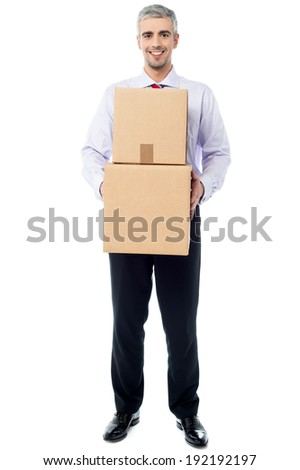 Smiling corporate man holding stack of boxes