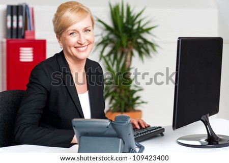 Smiling corporate woman typing on keyboard, working in office - stock photo