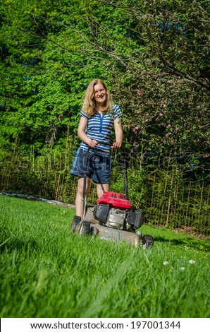 smiling country work woman and fuel grass cutting machine in garden seasonal work  - stock photo