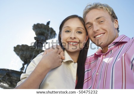 Smiling Couple, arms around, standing in Front of Fountain