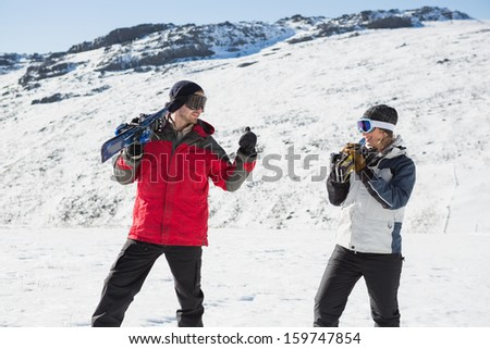 Smiling couple carrying ski boards on shoulders while walking on snow covered landscape - stock photo
