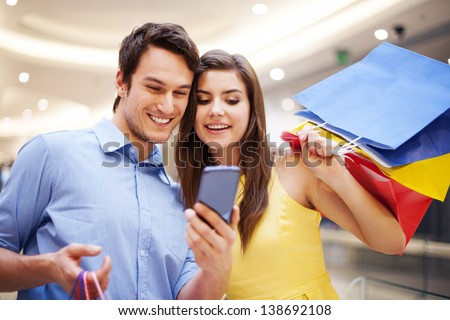 Smiling couple checking something on the mobile phone - stock photo
