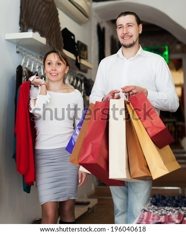 Smiling couple choosing clothes at clothing store