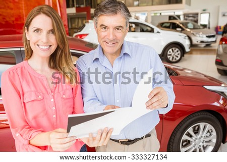 Smiling couple choosing the color of their new car at new car showroom