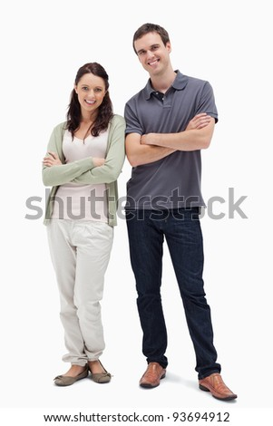 Smiling couple crossing their arms against white background - stock photo