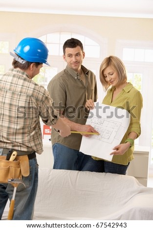 Smiling couple discussing ground plan of new home with builder.? - stock photo