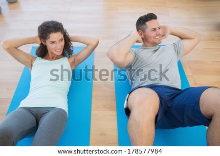 Smiling couple doing sit ups at a gym - stock photo