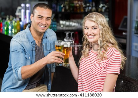 Smiling couple drinking beer in a bar - stock photo