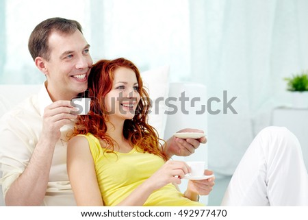 Smiling couple drinking coffee together and looking at something
