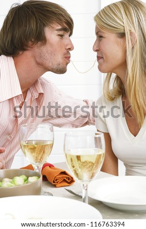 Smiling couple eating spaghetti with the wife eating from one end and the husband the other end of the same strand