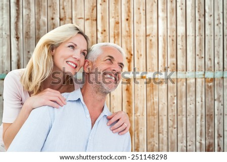 Smiling couple embracing and looking against wooden background in pale wood - stock photo