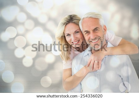 Smiling couple embracing and looking at camera against light circles on bright background - stock photo