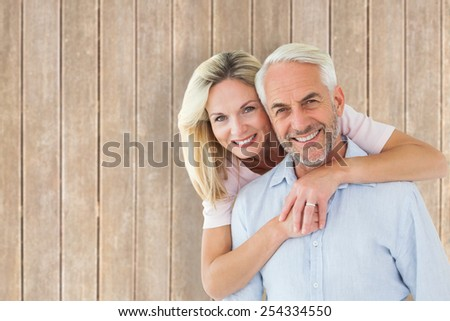 Smiling couple embracing and looking at camera against wooden planks - stock photo