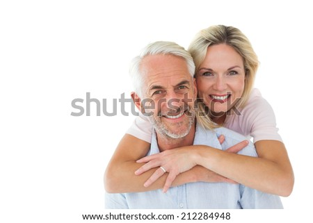 Smiling couple embracing and looking at camera on white background