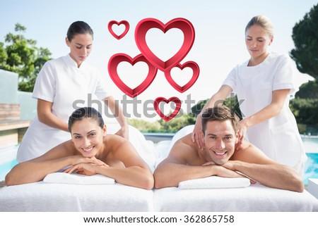 Smiling couple enjoying couples massage poolside against pink hearts - stock photo