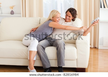 Smiling couple fighting for the remote in their living room