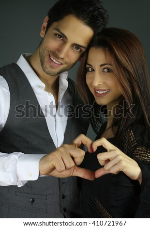 Smiling couple forming hearts shape