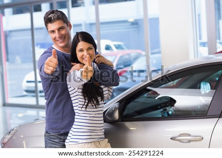 Smiling couple giving thumbs up at new car showroom - stock photo