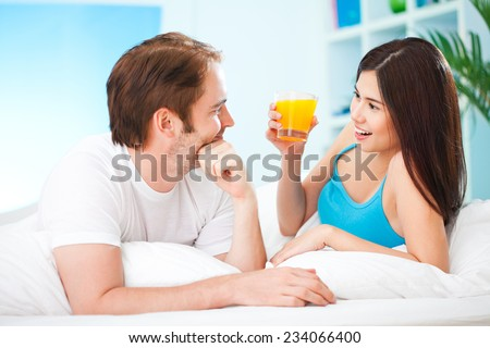 Smiling couple having a glass of orange juice in bed in the morning. - stock photo
