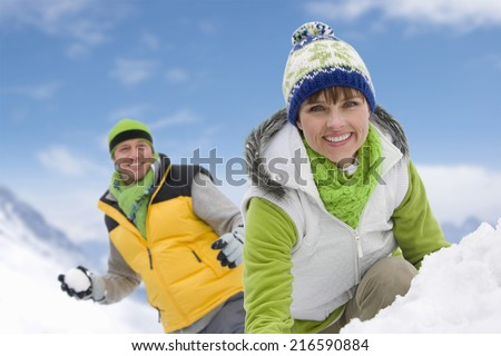 Smiling couple having snowball fight in snow together - stock photo