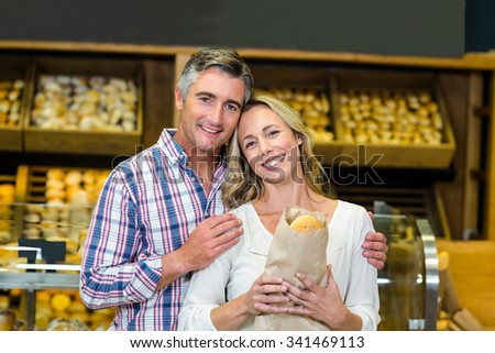 Smiling couple holding bread in paper bag in the supermarket