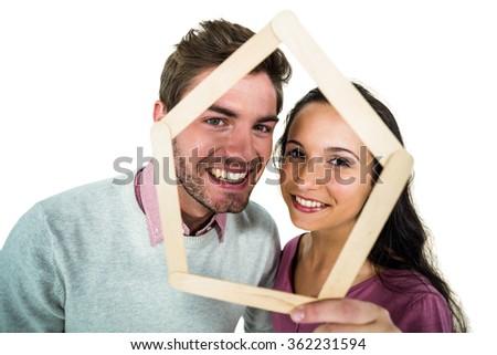 Smiling couple holding house shape on white screen - stock photo