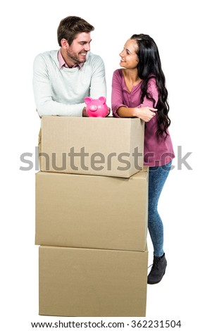 Smiling couple holding on boxes with piggy saver on white screen - stock photo