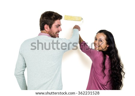 Smiling couple holding paint roller against white background - stock photo